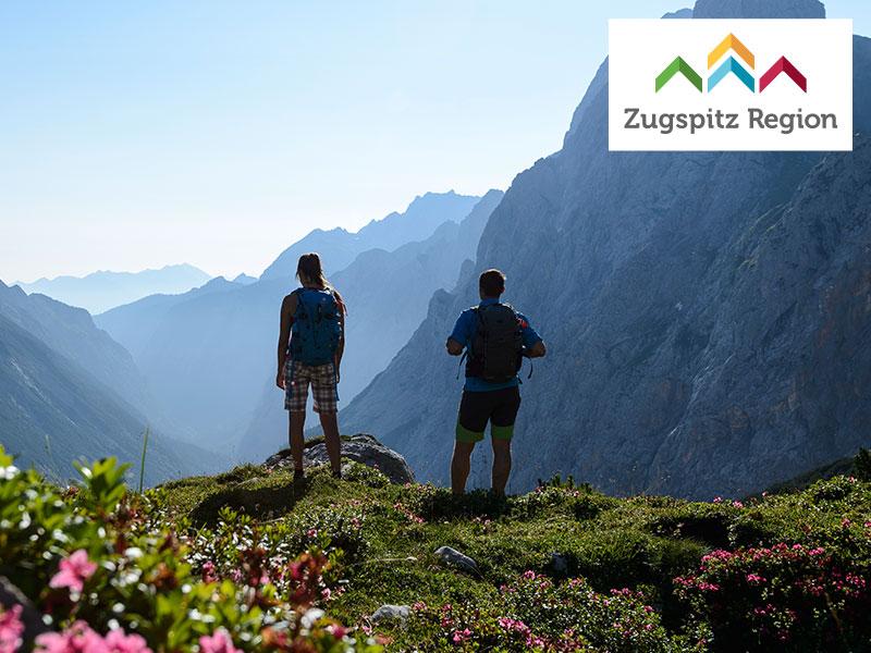 Großansicht - Wanderer auf Berggipfel mit Blick auf die Berge