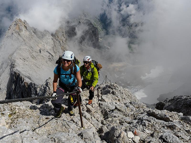 Großansicht - Wanderer auf alpinen Höhenweg mit Seil gesichtert
