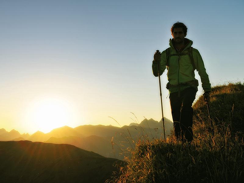 Großansicht - Wanderer mit Sonnenaufgang im Hintergrund