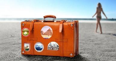 Großansicht - Oranger Reisekoffer auf Strand mit Frau im Hintergrund