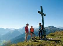 Drei Wanderer mit Gipfelkreuz