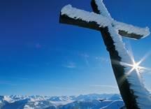 Verschneites Kreuz mit Alpenpanorama