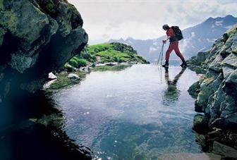Wanderer, der durch einen schmalen Bach in den Ötztaler Alpen wandert