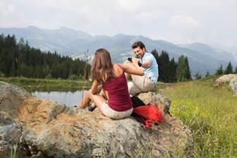 Pärchen sitztend auf Felsen an einem Bergsee in Wagrain