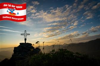 Gipfelkreuz vom 2095 Meter hohen Tristerkogel im Sonnenaufgang