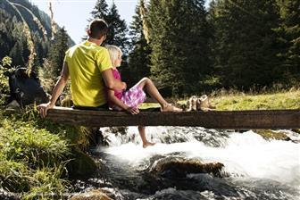 Vater mit Kind sitzend auf einer Brücke über den Bach im Schwarzachtal in den Zillertaler Alpen