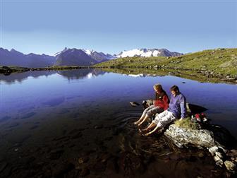Pärchen sitzend an einem Bergsee der Ötztaler Alpen