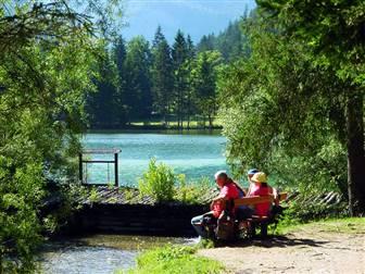 Pärchen sitzend auf Bank am See