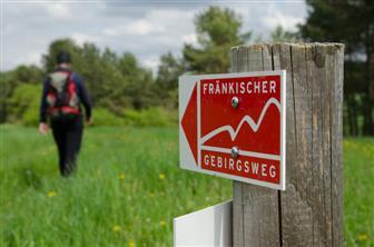 Rot-weißes Schild als Wegweiser für den Fränkischen Gebirgsweg
