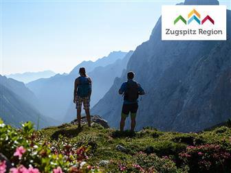 Wanderer auf Berggipfel mit Blick auf die Berge