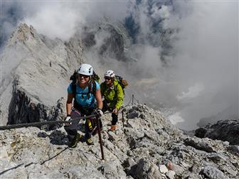 Wanderer auf alpinen Höhenweg mit Seil gesichtert