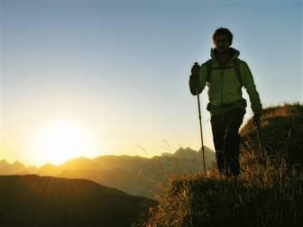 Wanderer mit Sonnenaufgang im Hintergrund