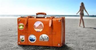 Oranger Reisekoffer auf Strand mit Frau im Hintergrund