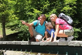 Familie auf einer Wandertour sitzend auf einem Holzsteg