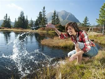 Frau hockend am See inmitten der Kitzbüheler Alpen
