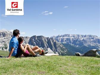 Pärchen sitzend auf Wiese mit Blick auf die Dolomiten