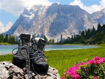 Bergschuhe auf Stein und im Hintergrund See und Berge