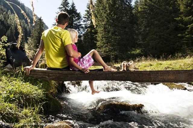 Großansicht - Vater mit Kind sitzend auf einer Brücke über den Bach im Schwarzachtal in den Zillertaler Alpen